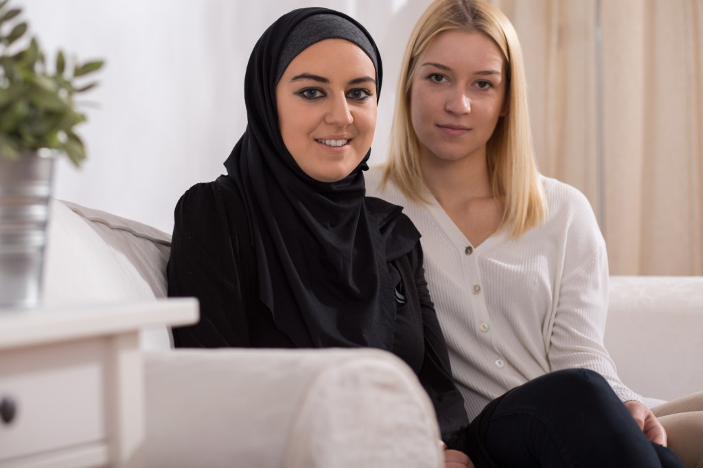 Pretty blond catholic girl and beautiful muslim in hijab