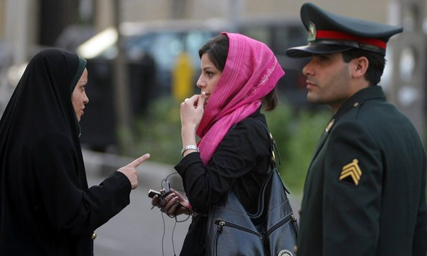 Courtesy of The Guardian, In a pre-summer ritual, an Iranian policewoman warns a young woman about her clothing and hair during a crackdown to enforce the Islamic dress code. Photograph: Majid/Getty Images