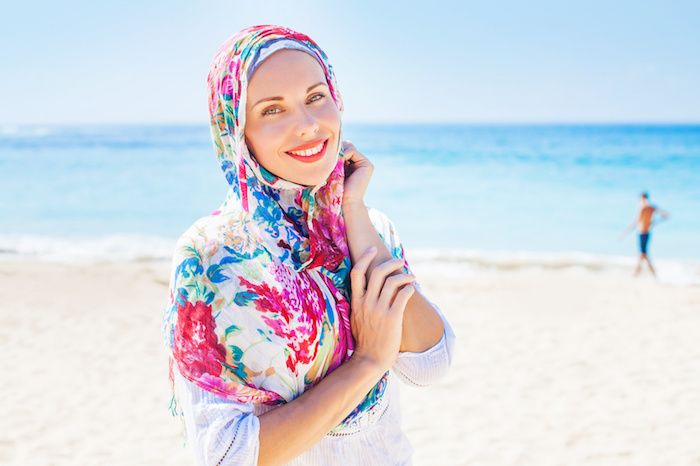 beautiful muslim caucasian (russian) woman wearing red dress relaxing on a beach