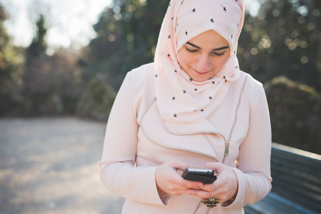 young beautiful muslim woman at the park in spring using smartphone connected online wireless