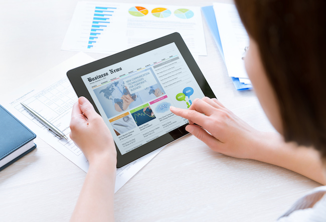 Businesswoman wearing casual shirt sitting at desk and looking latest business news on digital tablet in the office