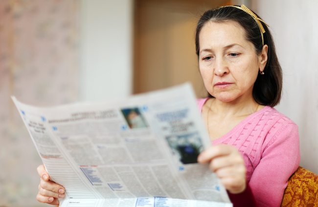 serious mature woman reading newspaper on sofa at home
