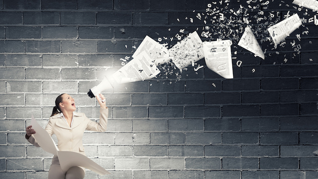Portrait of young businesswoman with newspaper screaming in megaphone