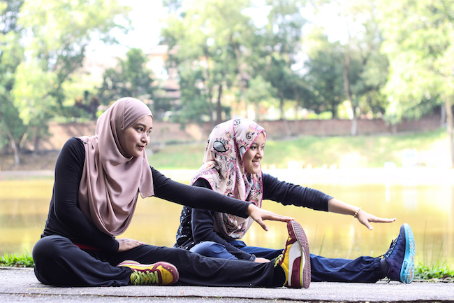 two young muslim women is stretching her body before they jogging in the morning.