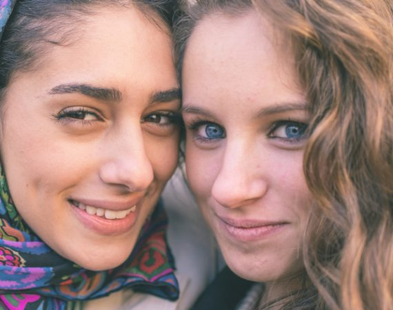 Portrait with two girls from different ethnicity. Muslims and christians people perfectly integrated