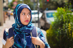 Beautiful young muslim woman wearing blue colored hijab and backpack, posing with thoughtful serious facial expression in street, outdoors urban background