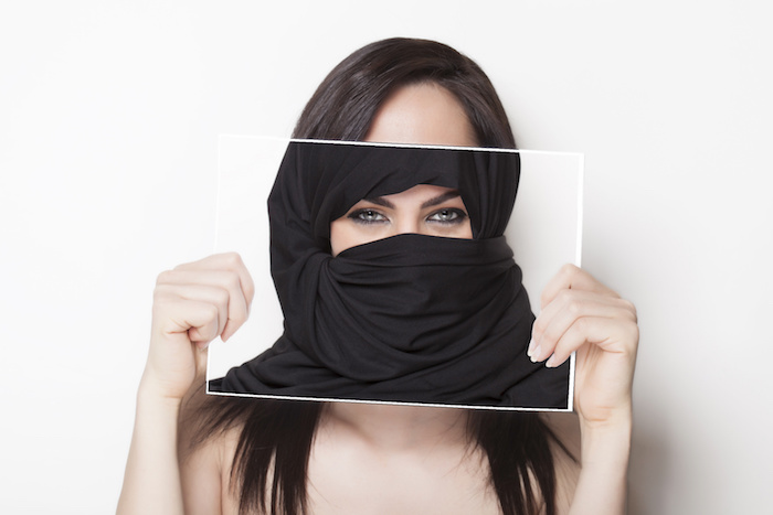 Beautiful girl holding a photo of herself wearing a burqa