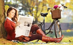 Young woman with bicycle sitting on a green grass and reading a newspaper