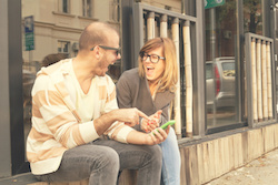 Couple using cellphone outdoors.