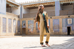 Young woman in Central Asia, in Uzbekistan the national dress, walks in the courtyard of the madrasah, the city of Khiva.