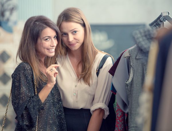 Two smiling friends enjoy in clothing shop